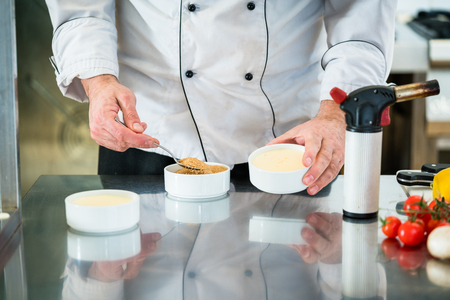 Chef or Patissier preparing a creme brulee putting sugar on top Stock Photo