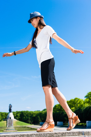 Low-angle view of young Asian woman standing on one leg outdoors in summer
