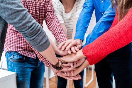 Studenten in universiteit die hand samen stapelen, die een team zijn Stockfoto