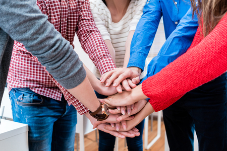 working on school project: Students in college stacking hand together, being a team
