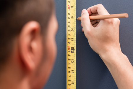 Young handyman sizing with tape measure and pencil