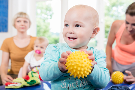Babies with pacifier in toddler group playing with toys in baby course