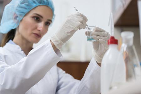 現代の化粧品工場の所で作業中に革新的な効率的な物質を作成する専用の女性化学者 写真素材