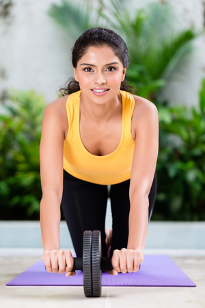 elasticidad: Young woman doing stretching exercise while sitting on yoga mat indoors
