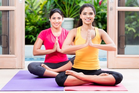 Two young women sitting on mats in lotus position during yoga practice indoors