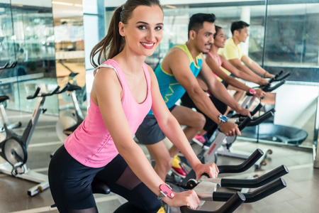Side view of a beautiful fit young woman smiling while pedaling during cardio workout at indoor cycling group class in a modern fitness club