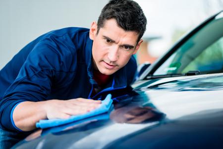 깨끗한 파란 차의 표면을 건조하고 연마하기 위해 흡수성 부드러운 수건을 사용하는 젊은 남자