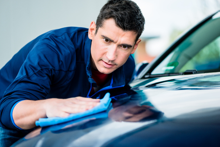 Young man using an absorbent soft towel for drying and polishing the surface of a clean blue car Foto de archivo