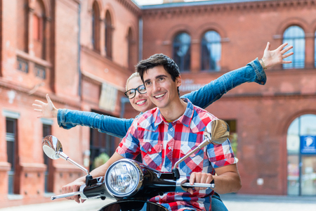Young tourists, woman and man, doing sightseeing tour in Berlin on Vespa