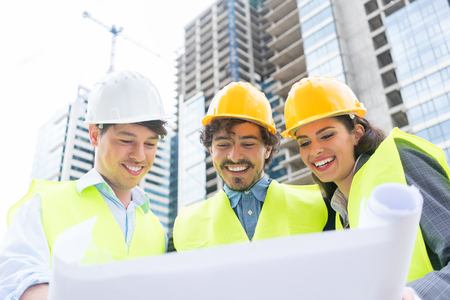 Architects and civil engineers with ground plot on construction site of highrise building Stock Photo