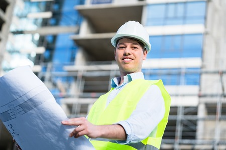 Construction engineer studying floor plan in front of building shell at construction site
