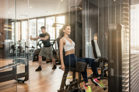 Attractive young woman sitting at the abductor machine while exercising for toned in a trendy fitness club with modern equipment