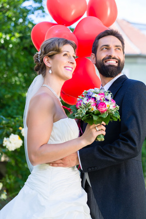 marrying: Bride and groom at wedding with read helium balloons Stock Photo