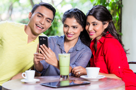 Indian girl showing pictures on smart phone to her friends in an Indian cafe