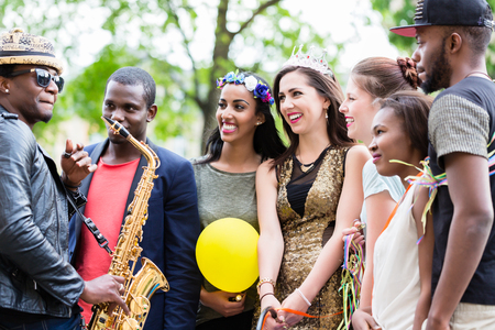 Street artist playing saxophone for a multi-ethnic party group of young women on a hens night