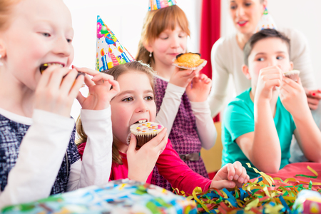 Children grabbing muffins at birthday party and cake, the kids are wearing hats, balloons and paper streamers for decoration Stock Photo