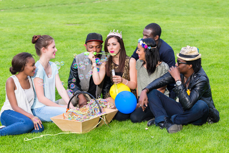 Multicultural group of men and women, sitting on lawn, blowing soap bubbles Stok Fotoğraf