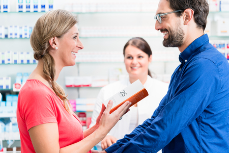 Woman and man buying drugs in pharmacy being advised by apothecary
