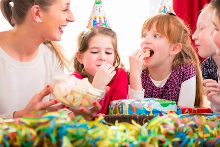 Kinderen op verjaardagsfeestje knabbelen snoepjes dragen feestmutsen