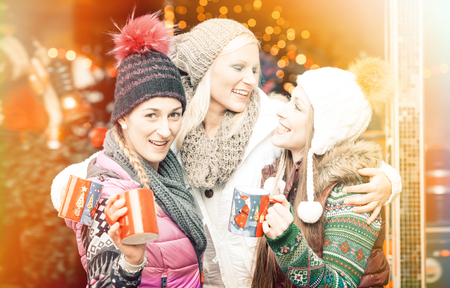 Women drinking mulled wine in mugs on German Christmas Market in front of bright lights