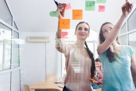 Two proficient female co-workers posting sticky notes in the interior of a shared office space for task prioritization and better time management