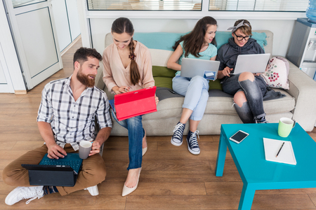 hubs: Happy young people laughing while sharing a collaborative office space as co-workers in a modern hub with WI-FI wireless network for digital nomads