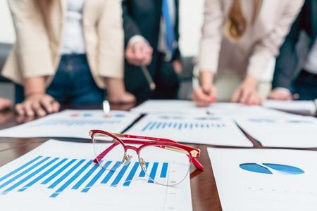 Close-up de óculos com quadros vermelhos em um gráfico de barras impressas mostrando progresso durante uma reunião de analistas de negócios, no escritório de uma empresa de sucesso