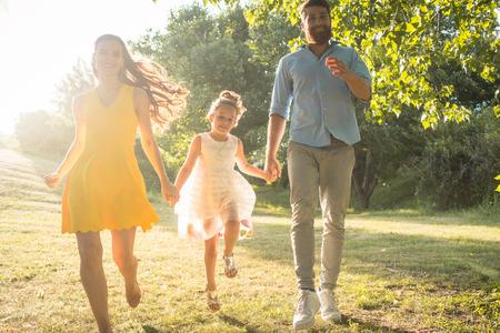 Volledige lengte van twee gelukkige ouders met een gezonde levensstijl die vrijetijdskleding dragen terwijl samen het lopen, met hun leuke dochter in een zonnige dag van de zomer Stockfoto