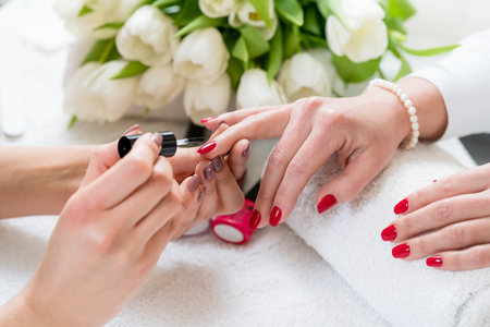 Close-up of the hands of a skilled manicurist applying elegant red nail polish, on the medium length nails of a young woman in a trendy beauty salon Banque d'images
