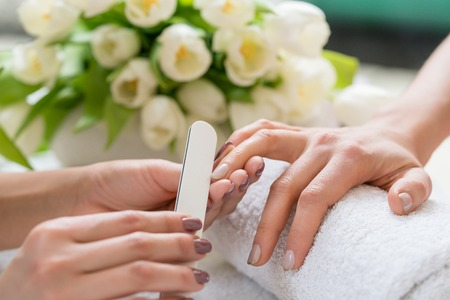 Nahaufnahme der Hände eines qualifizierten Maniküristen, der die Nägel einer jungen Frau mit einem weißen Puffer in einem modischen Nagelsalon archiviert