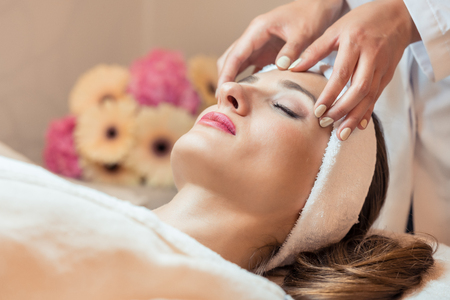 Close-up of the face of a beautiful woman relaxing under the gentle touch of the therapist, during rejuvenating facial massage in a modern beauty center