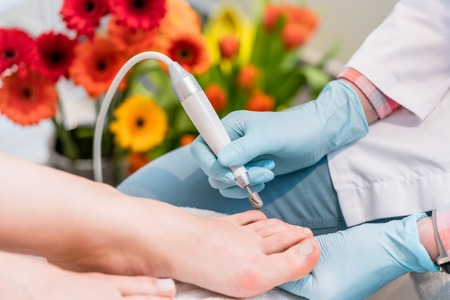 Close-up of the hands of a pedicurist wearing sterile surgical gloves while using a toe nail clipper, while shaping the nails of a female customer in a beauty salon