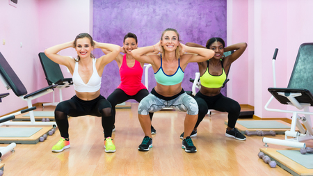 Full length front view of four women doing squats with hands behind the head during workout group class, in a modern health club for ladies only Stock Photo