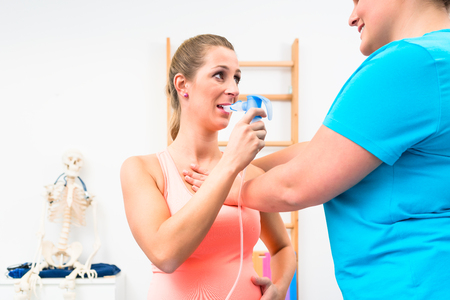 Woman taking pulmonary function test with mouthpiece in her hand