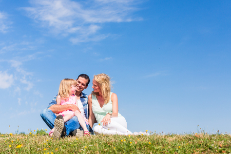 them: Girl on dads lap, Mom sitting next to them in field Stock Photo
