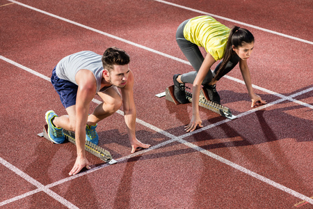 Male and female athlete in starting position at starting block of cinder track Stock Photo