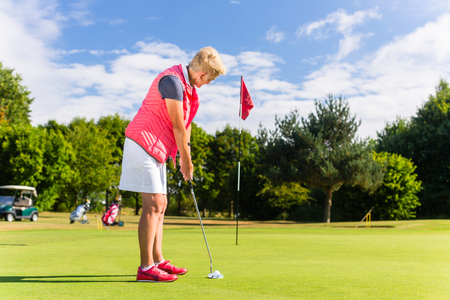 Senior golf playing woman putting on green Stock Photo