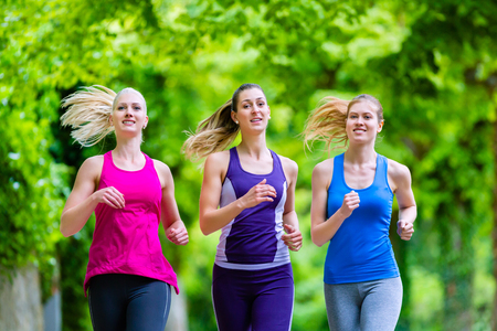 Three motivated women jogging in green forest