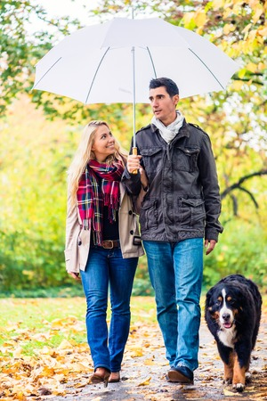 Woman and man having walk with dog in autumn or fall rain