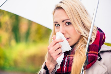 Woman having cold or flu due to bad autumn or fall weather Stock Photo