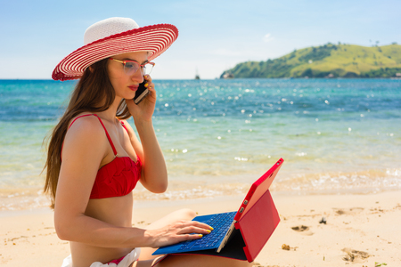 Fashionable young woman talking on mobile phone while using a tablet on the beach in a sunny day of summer in Flores Island, Indonesia Stock Photo