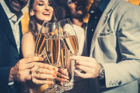 Hombres y mujeres celebrando cumpleaños o fiesta de año nuevo mientras tintinean vasos con vino espumoso Foto de archivo