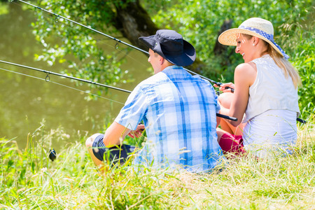 Couple, woman and man, sitting at river side with fishing rods angling for sport Stock Photo