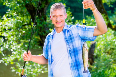 Sport fisherman showing his catch dangling from the fishing rod Stock Photo