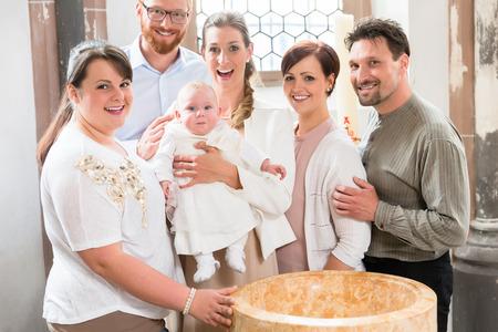 Genitori e padrini stanno al fonte battesimale con il bambino in una chiesa