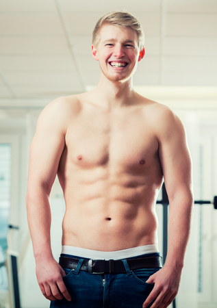Trained athlete showing his muscles and six pack in health club gym