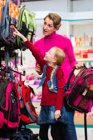 Family buying school satchel or bag in store preparing for first day in school