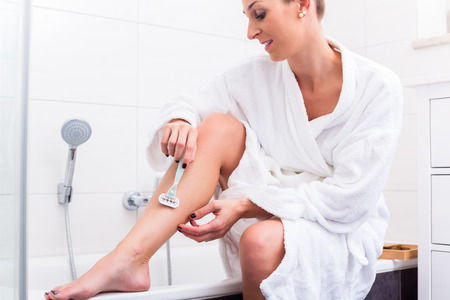 Woman sitting at edge of tub in bathroom using epilator for depilation