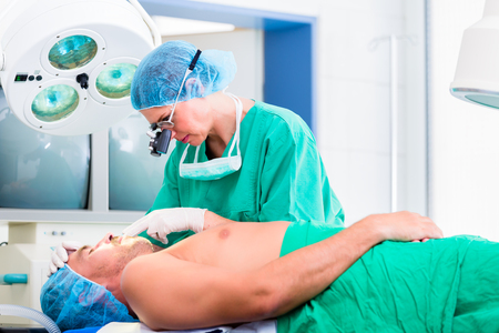 orthopedist: Orthopedic surgeon doctor operating patient in surgery or hospital Stock Photo