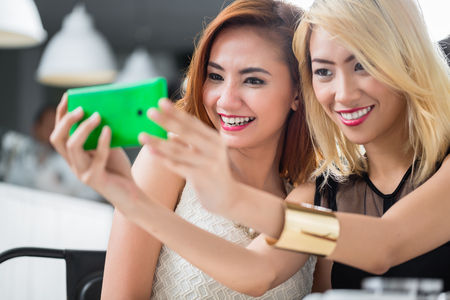 Two elegant Asian women posing for a selfie together on a mobile phone as they sit enjoying drinks in a restaurant